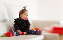 Portrait toddler baby girl playing on the sofa. Royalty Free Stock Photography