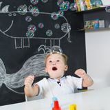 Portrait of cute toddler boy amazed by milky bubbles. Stock Photo