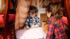 Portrait of cute toddler boy playing with elder sister in tent at bedroom. Portrait of toddler boy playing with elder sister in tent at bedroom Royalty Free Stock Photos