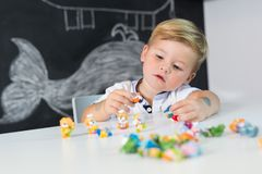 Portrait of cute toddler boy playing with toys at the desk at home. Stock Photo