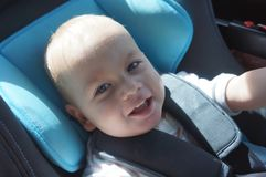 Portrait of cute toddler boy sitting in car seat. Child transportation safety.  royalty free stock photography