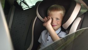 A cheerful baby waving his hand while sitting in a children`s car seat. Portrait of cute toddler boy sitting in car seat. Child transportation safety. A stock footage