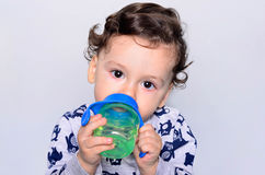 Portrait of a cute toddler drinking water from the bottle. Royalty Free Stock Photos