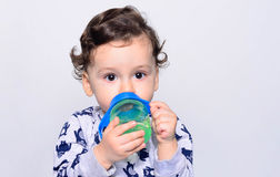 Portrait of a cute toddler drinking water from the bottle. Royalty Free Stock Image