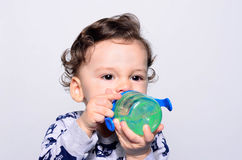 Portrait of a cute toddler drinking water from the bottle. Stock Photo