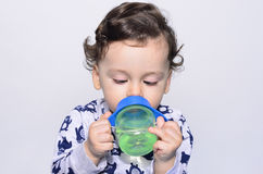 Portrait of a cute toddler drinking water from the bottle. Royalty Free Stock Images