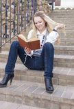 Portrait of Cute and Tranquil Caucasian Blond Woman Reading Book While Sitting Straight on Stairs Outdoors Stock Photo
