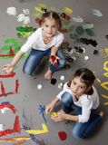 Portrait of cute twin girls with finger paintings Stock Image