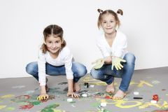 Portrait of cute twin girls with finger paintings. In a studio Stock Images