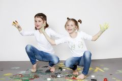 Portrait of cute twin girls with finger paintings. In a studio Stock Photo