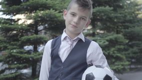 Portrait cute well-dressed boy standing on the street holding the soccer ball and purse. Serious young man stock footage