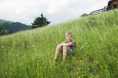 Portrait of cute white blond boy sitting at grassy hill stock photos