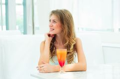 Portrait of a cute woman in a city cafe. Portrait of a young pretty woman in a small café, with a bright blue drink in hand Royalty Free Stock Images
