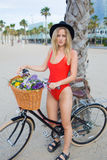 Portrait of cute woman dressed in trendy red swimsuit standing with retro bike on the beach stock photography