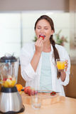 Portrait of a cute woman eating a fresh strawberry Royalty Free Stock Images