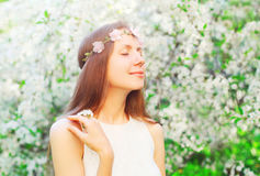 Portrait cute woman with floral headband enjoying smell spring flowers Royalty Free Stock Image