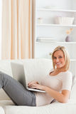 Portrait of a cute woman lying on a sofa Royalty Free Stock Image