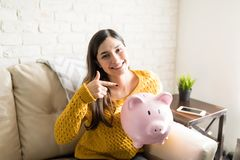 Woman Saving Money Using Piggy Bank. Portrait of cute woman pointing at pink piggybank while smiling at home stock photography