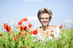 Portrait of cute woman in poppy field Stock Photos