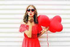 Portrait cute woman in red dress sends air kiss with balloon heart shape over white. Background Stock Images