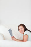 Portrait of a cute woman on a sofa holding a book Stock Photos
