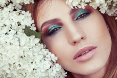 Portrait of cute woman with vogue makeup in many flowers. In the park. Outdoor spring or summer photo Stock Photos