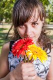 Portrait of a cute women with three flowers Royalty Free Stock Photography