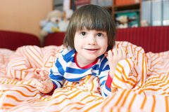 Portrait of cute 2 years child in bed at home Stock Photography