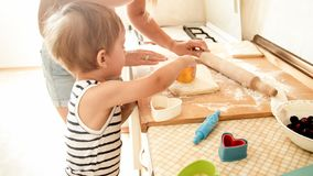 Portrait of cute 3 years old toddler boy cooking cookies with mother. Family cooking and baking. Portrait of 3 years old toddler boy cooking cookies with mother royalty free stock image