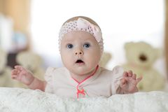 Portrait of a cute young baby wearing a bodysuit shirt lying on belly in nursery room royalty free stock image