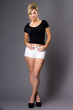 Portrait of cute young blonde, in white shorts and dark top on g Stock Photos
