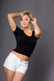 Portrait of cute young blonde, in white shorts and dark top on g Royalty Free Stock Images