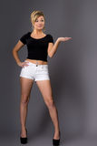Portrait of cute young blonde, in white shorts and dark top on g Royalty Free Stock Photos
