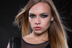 Portrait of a cute young blonde woman. Posing in a studio dressed in a black leather suit royalty free stock images