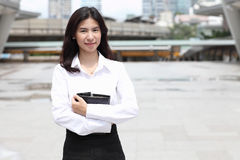Portrait of cute young business woman outdoor with her note book Stock Photos