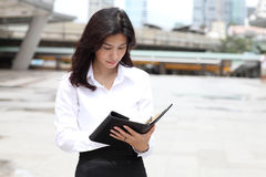 Portrait of cute young business woman outdoor read massage on he. Portrait of cute young business woman outdoor read massage on note book Royalty Free Stock Photos