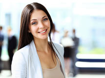 Portrait of a cute young business woman smiling, in an office environment Royalty Free Stock Photography