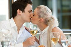 Cute couple kissing at dinner table. royalty free stock photography