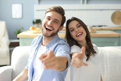 Portrait of cute young couple pointing and laughing, sitting in sofa.  royalty free stock photos