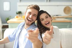 Portrait of cute young couple pointing and laughing, sitting in sofa.  stock images