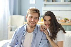 Portrait of cute young couple sitting in sofa.  royalty free stock image