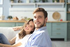 Portrait of cute young couple sitting in sofa.  stock photos
