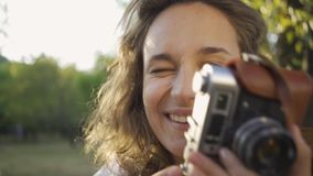 Portrait of cute young female photographer with curly hair looking at the camera while taking photo using old camera in. Attractive young photographer with curly stock video