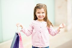 Cute young girl with shopping bags outside a mall. Portrait of a cute young girl carrying shopping bags and smiling while standing outside a mall Stock Image