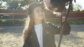 Portrait of cute, young girl in hat caresses black mare`s head stock video footage