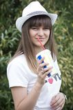 Portrait cute young girl in hat with coctail in hand smiles on park nature background. Young girl drinks drink outdoors. Stock Photos