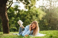 Portrait of a cute young girl laying on a grass at the park. Talking on mobile phone Stock Photos
