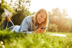 Portrait of a cute young girl laying on a grass at the park. Using mobile phone Royalty Free Stock Photo