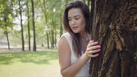 Portrait cute young girl with long brunette hair wearing a long white summer fashion dress standing next to a tree in stock footage