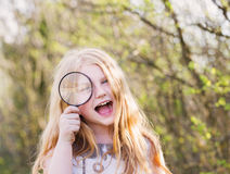 Portrait of a cute young girl looking through magnifying glass Stock Image